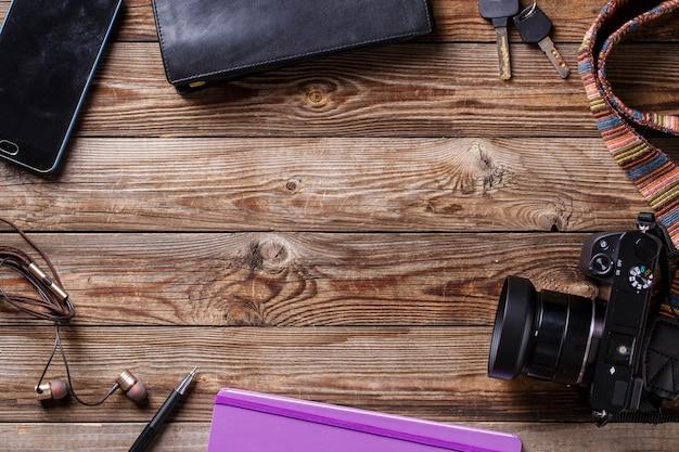 Концепция путешествия - наушники, фотоаппарат, альбом для рисования, кошелек, карандаш и ключи на деревянных фоне. плоская планировка фото сверху с copyspace в центре.