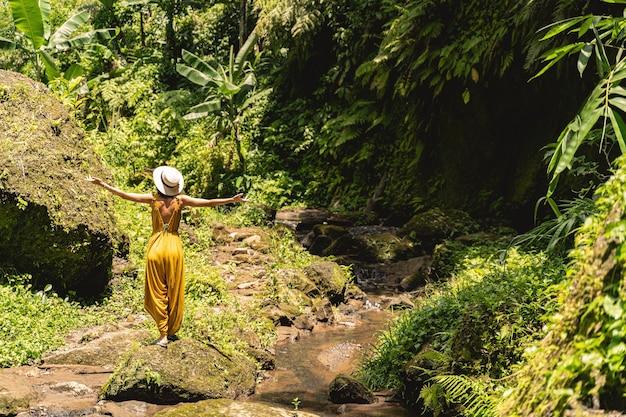 여행 개념입니다. 습한 공기를 즐기면서 돌 위에 서서 깊은 호흡을 하는 친절한 젊은 여성