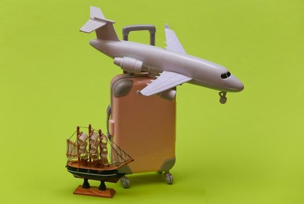 여행 개념입니다. 녹색 배경에 미니 플라스틱 여행 가방, 배, 비행기. 미니멀한 스타일