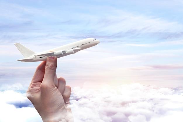 손과 하늘 배경에 여행 개념 미니어처 비행기