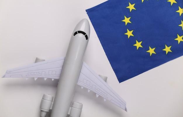 Концепция путешествия. пассажирский самолет и флаг евросоюза на белом фоне