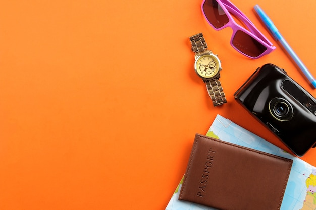 旅行のコンセプトパスポート、地図、カメラ、サングラスを明るいオレンジ色の背景に。上面図。テキストの場所