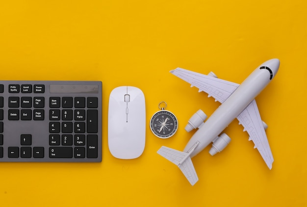 Travel concept. pc keyboard and air plane, compass on yellow