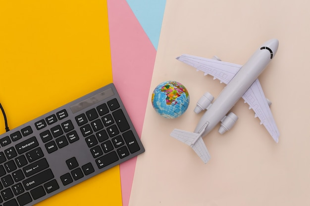 Travel concept. pc keyboard and air plane, globe on colored table