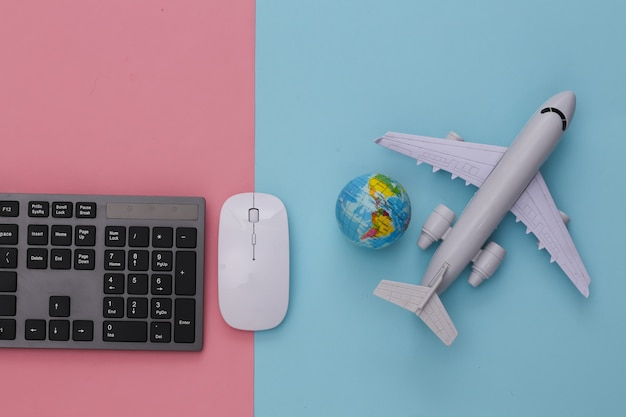 Travel concept. pc keyboard and air plane, globe on pink blue