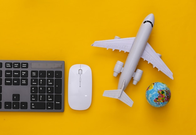 Travel concept. pc keyboard and air plane, globe on yellow