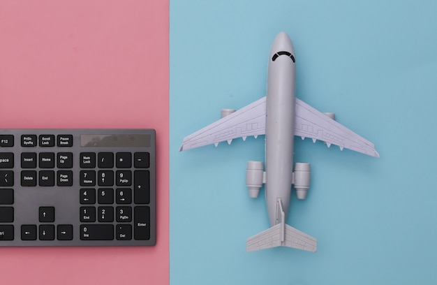 Travel concept. pc keyboard and air plane on pink blue