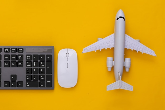 Travel concept. pc keyboard and air plane on yellow