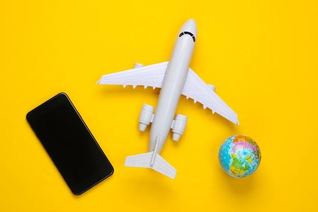 旅行のコンセプト。黄色い表面に飛行機の置物、地球儀、スマートフォン。上面図