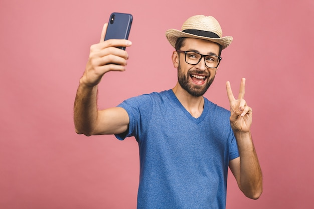 Travel concept. portrait of cheerful young man in straw hat taking selfie with smartphone isolated over pink background.