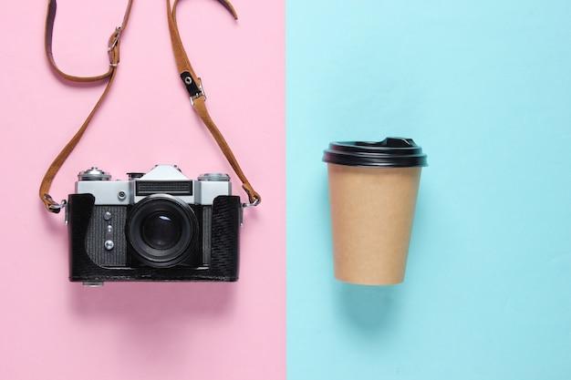 旅行の概念。レトロなカメラとブルーピンクのクラフトコーヒーカップ。上面図