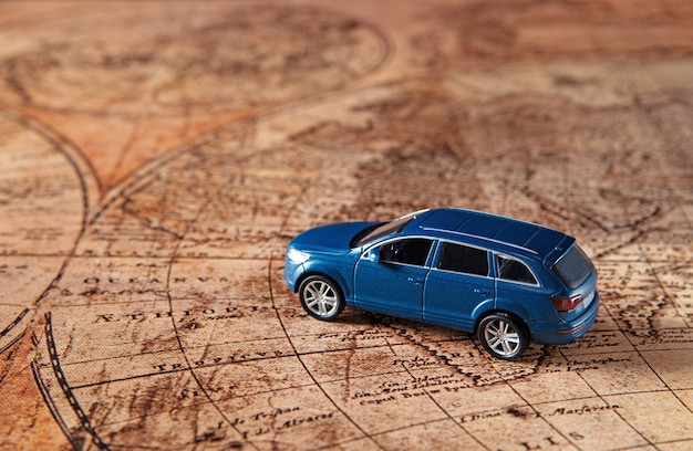 Travel concept - small blue sport toy car on the old map. copy space.