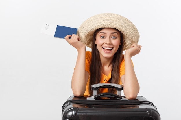Travel concept. studio portrait of pretty young woman holding passport and luggage. isolated on white