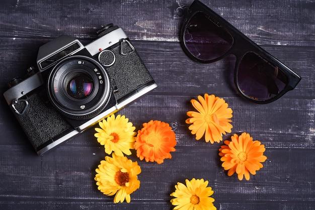 旅行の概念。夏の花、カメラ、暗い背景の木のサングラス。上面図