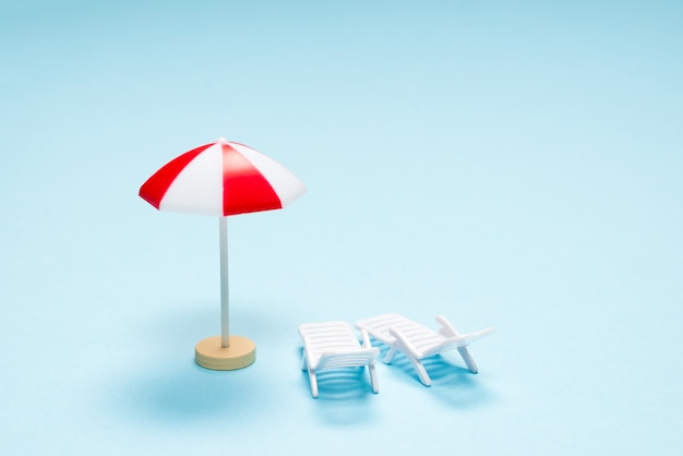 Концепция путешествия. шезлонг, красный зонт на синем фоне. скопируйте пространство.