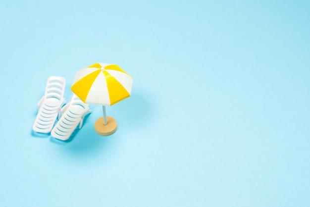 Концепция путешествия. шезлонг, желтый зонт на синем фоне. скопируйте пространство.