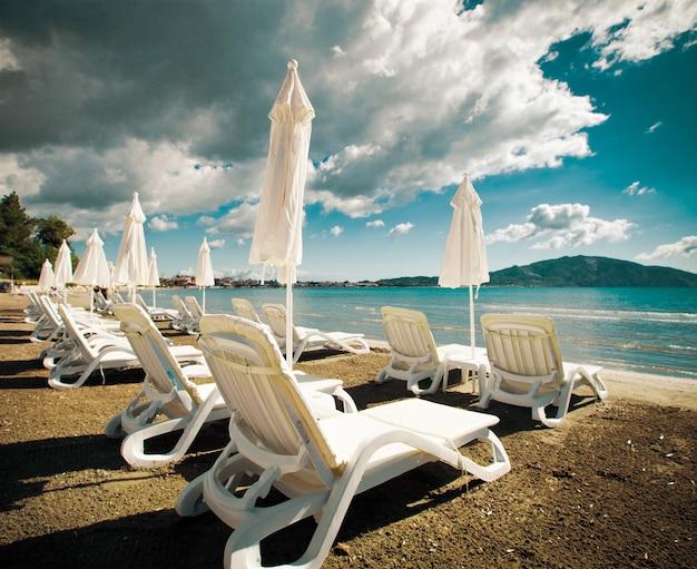 Концепция путешествия - шезлонги с зонтиками на красивом пляже, остров закинф, греция Premium Фотографии