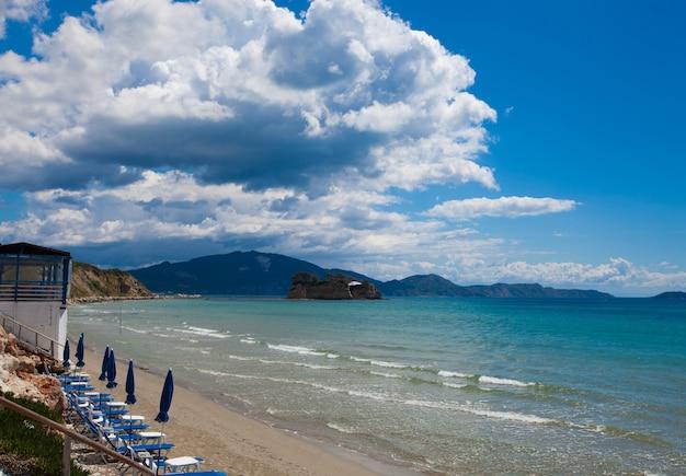 Концепция путешествия - шезлонги с зонтиками на красивом пляже, остров закинф, греция