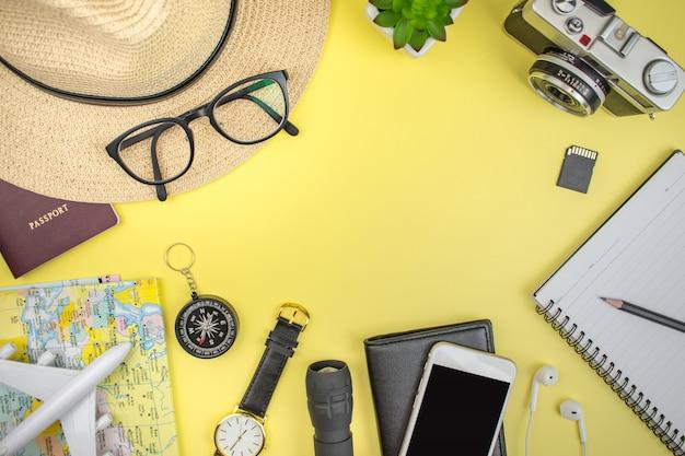 旅行のコンセプト。帽子、メガネ、ビンテージカメラ、パスポート、地図、ノートブック、スマートフォン、時計、コンパス、コピースペースと黄色の背景の財布と旅行アクセサリー。