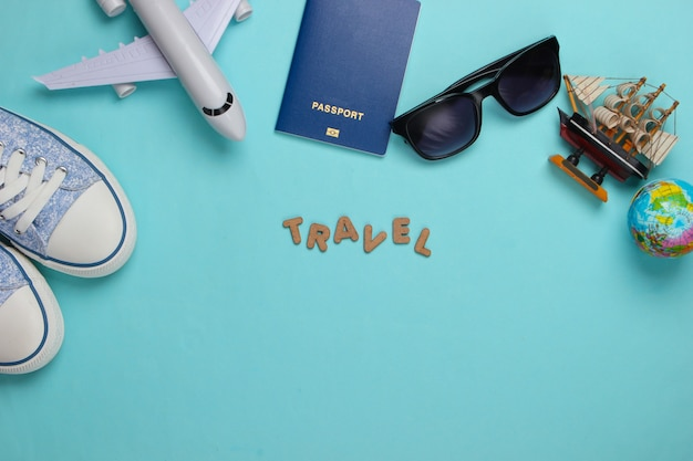 Travel concept. traveler accessories on a blue with the word travel. cruise, air flight, vacation flat lay. copy space