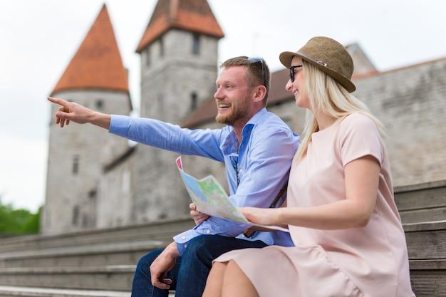 Концепция путешествия - два счастливых туриста сидят с картой города