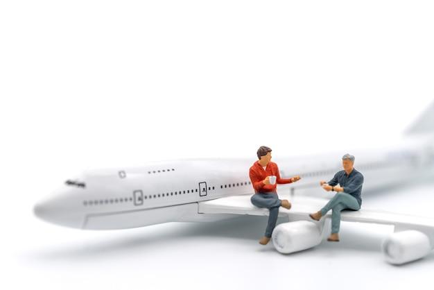 여행 개념입니다. 흰색 바탕에 비행기 장난감 모델의 날개에 앉아 커피 한 잔을 들고 이야기하는 두 남자 미니어처 그림.