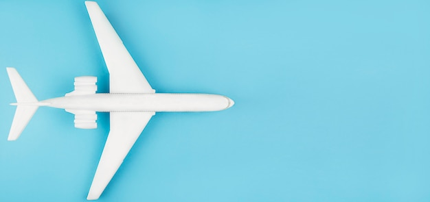 Travel concept. white plane on a blue table, flat lay, copy space. summer holidays, tourism.