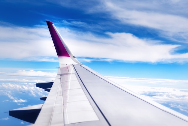 Travel concept. wing of airplane flying above the clouds in the sky. copy space