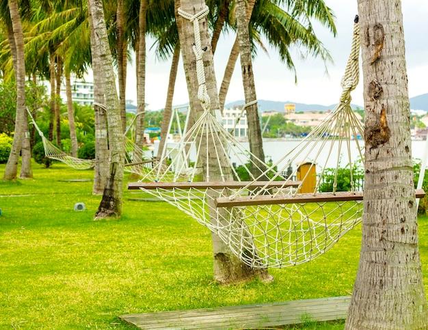 배경에 청록색 물이 있는 열대 해변에서 해먹이 있는 여행 컨셉입니다.