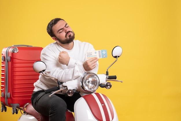 Концепция путешествия с амбициозным человеком, сидящим на мотоцикле с чемоданом на нем, показывая билет на желтом