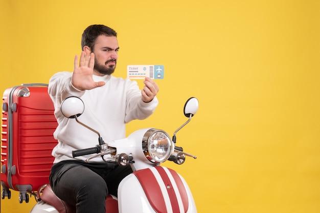 Concetto di viaggio con un uomo arrabbiato seduto su una moto con la valigia sopra che mostra il biglietto su giallo
