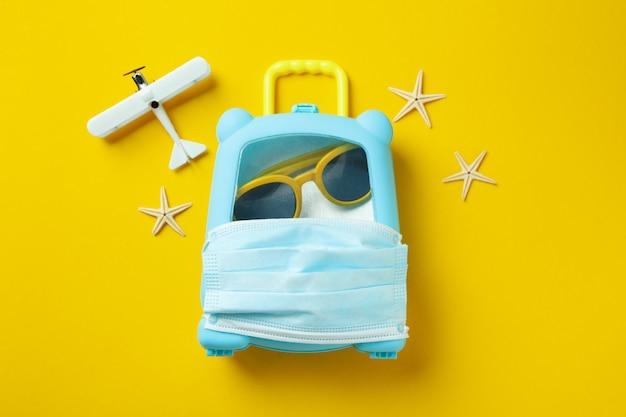 노란색 배경에 의료 마스크 가방 여행 컨셉