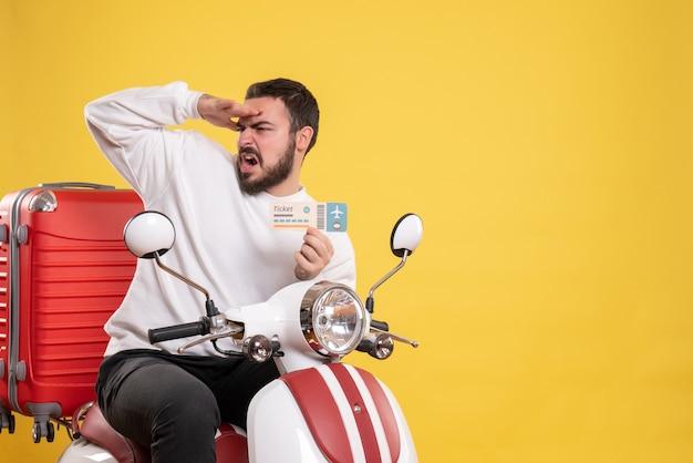 Концепция путешествия с сосредоточенным человеком, сидящим на мотоцикле с чемоданом на нем, показывая билет на желтом