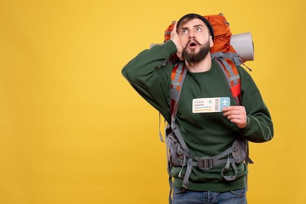Концепция путешествия с сосредоточенным молодым парнем с пакетом и показывающим билетом на желтом
