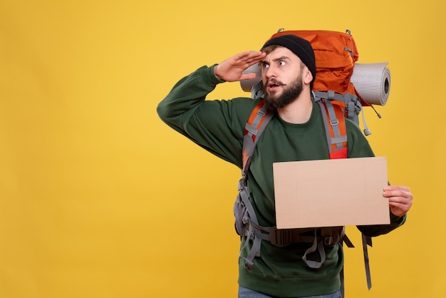 Travel concept with concentrated young guy with packpack and holding free space for writing looking up on yellow