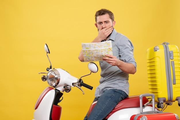 スーツケースを持ってバイクに座って、黄色の地図を保持している混乱した若い男と旅行の概念