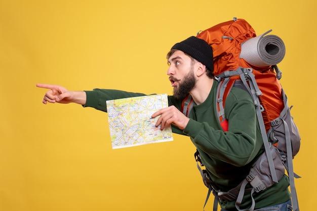 Packpack과 함께 호기심이 많은 젊은 남자와 노란색의 왼쪽에 무언가를 가리키는지도를 보여주는 여행 개념