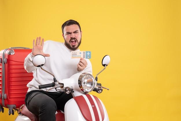 Concetto di viaggio con un uomo emotivamente confuso seduto su una moto con la valigia sopra che mostra il biglietto su giallo