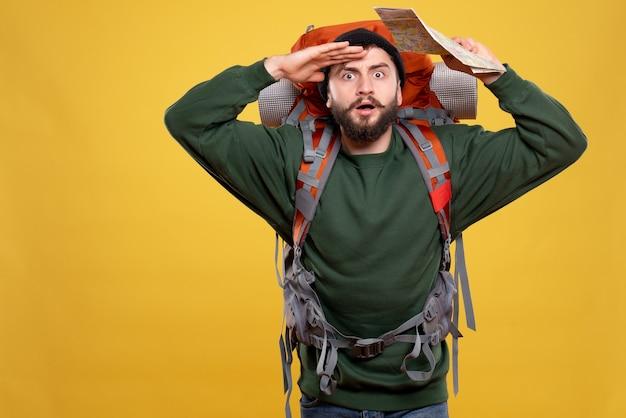 パックパックと黄色の地図を保持している焦点を当てた若い男と旅行の概念