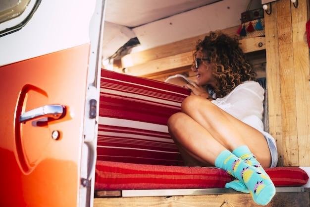 幸せな代替の人々のライフスタイルと旅行の概念-美しい魅力的な若い白人女性が笑顔で外を見て赤い手作りの木製ヴィンテージバンの中に座っています