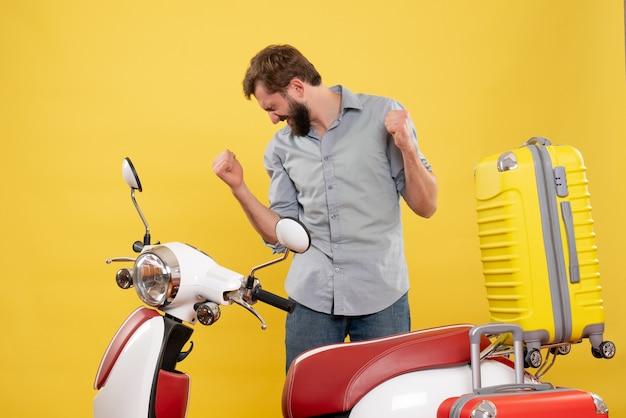黄色のチケットを保持しているスーツケースとバイクの後ろに立っている幸せな感情的な若い男と旅行のコンセプト