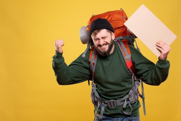 パックパックと黄色に書かずにシートを保持して幸せな感情的な若い男と旅行の概念