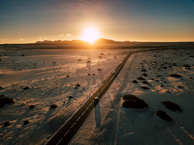 ランドマークと砂漠を横切る長い黒いアスファルト道路とバックゴーランドの夕日のある旅行のコンセプト-風光明媚な道路を車で運転して移動する