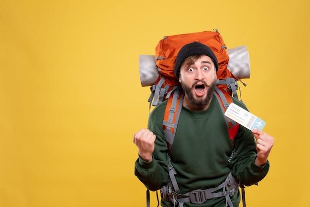 Packpack과 노란색에 티켓을 들고 긴장된 감정적 인 젊은 남자와 여행 개념
