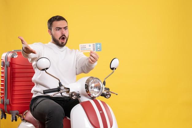 Concetto di viaggio con un uomo nervoso seduto su una moto con la valigia sopra che mostra il biglietto su giallo