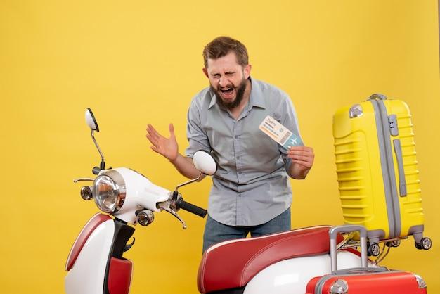 黄色のチケットを保持しているスーツケースを持ってバイクの後ろに立っている神経質な若い男と旅行の概念