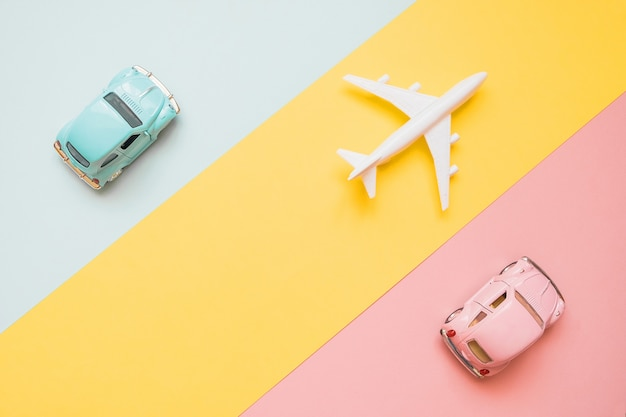 Travel concept with plane and cars on blue, yellow and pink