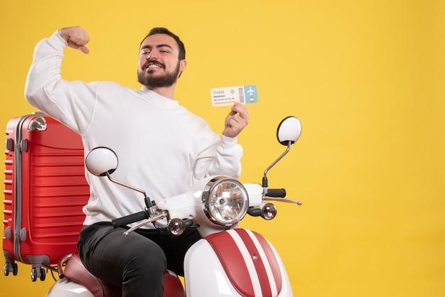 Концепция путешествия с гордым человеком, сидящим на мотоцикле с чемоданом на нем, показывая билет на желтом