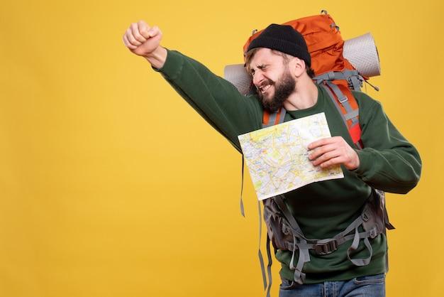 Концепция путешествия с гордым молодым человеком с рюкзаком и картой на желтом