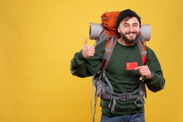 パックパックで若い男を笑顔で、黄色で大丈夫なジェスチャーをする銀行カードを示す旅行の概念
